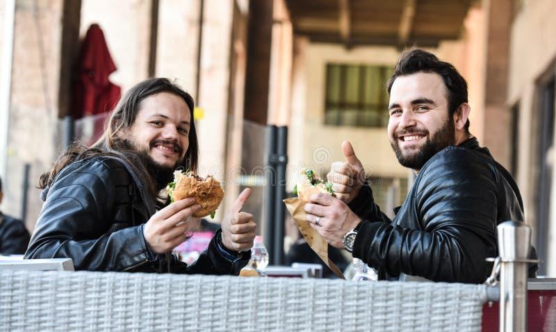 Zwei hungrige Freunde/Touristen essen das Mittagessen zusammen und das Lächeln stockfoto