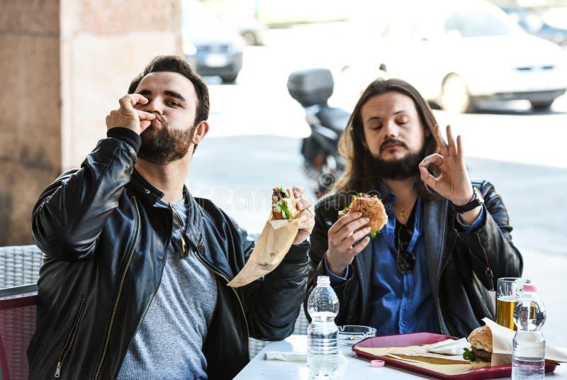 Zwei hungrige Freunde/Touristen essen das Mittagessen zusammen und machen ein Zeichen mit ihren Händen stockfoto