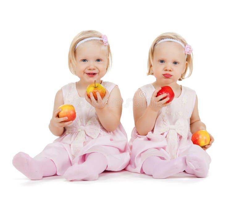 Zwei identisches Zwillingsmädchen, das mit Äpfeln spielt lizenzfreie stockfotos