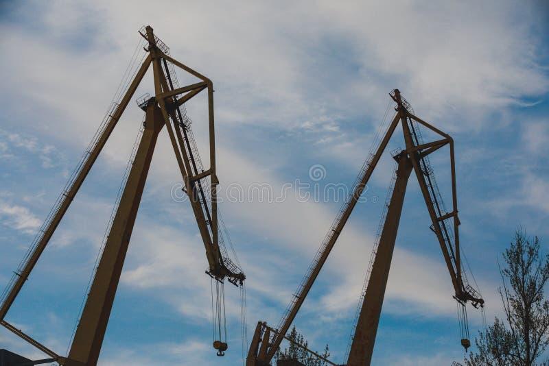 Zwei Industriebaukräne auf Hintergrund des blauen Himmels stockfotos