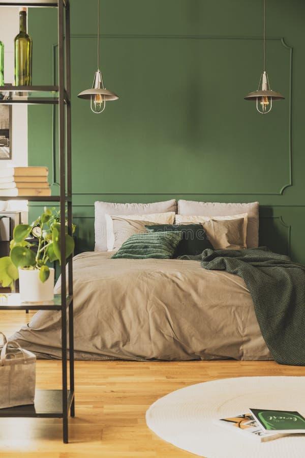 Zwei industrielle Lampen ?ber bequemem Doppelbett mit gem?tlicher Bettw?sche, Kopienraum auf leerer Wand lizenzfreies stockbild
