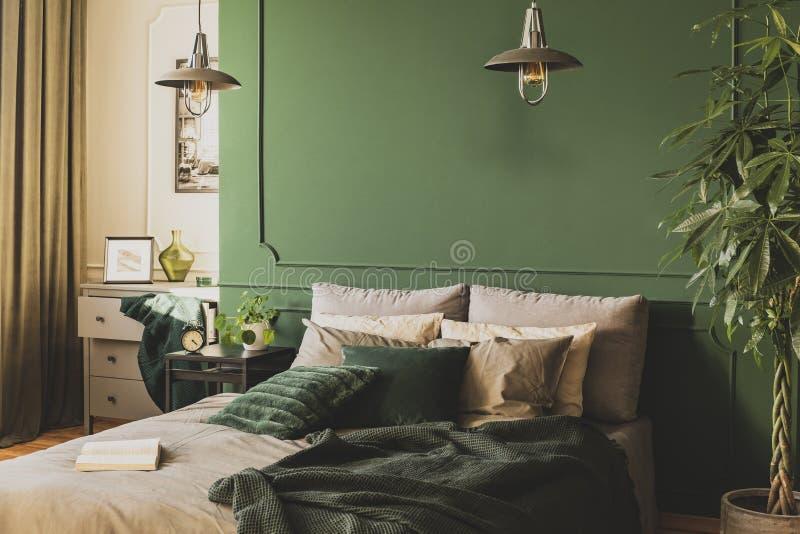 Zwei industrielle Lampen ?ber bequemem Doppelbett mit gem?tlicher Bettw?sche, Kopienraum auf leerer Wand stockfotos