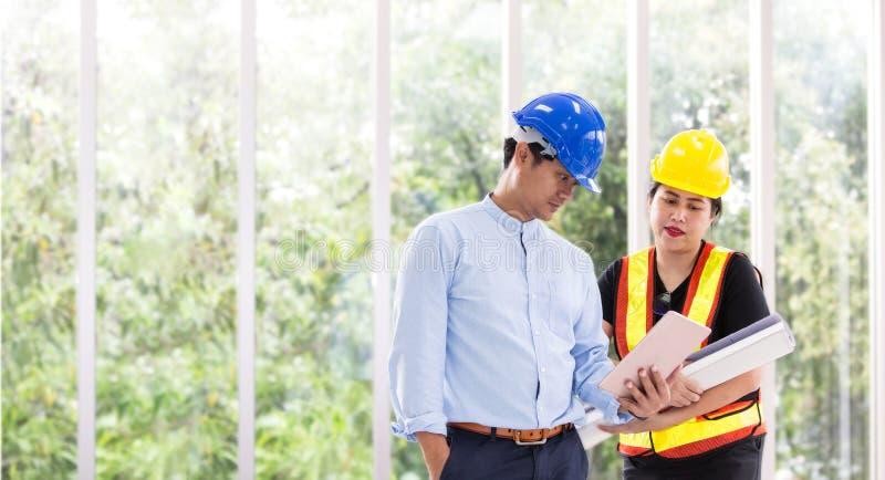 Zwei Ingenieure, die draußen mit einer Tablette arbeiten Zwei Arbeitskräfte passen Bauplan auf im Büro Asiatisches Geschäft stockbild
