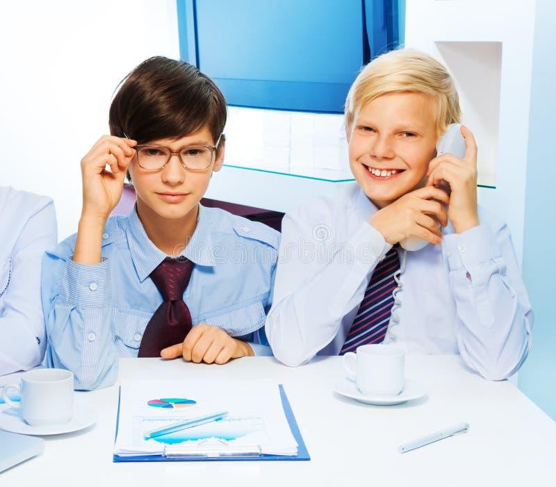 Zwei intelligente Kinder im Büro lizenzfreie stockfotografie