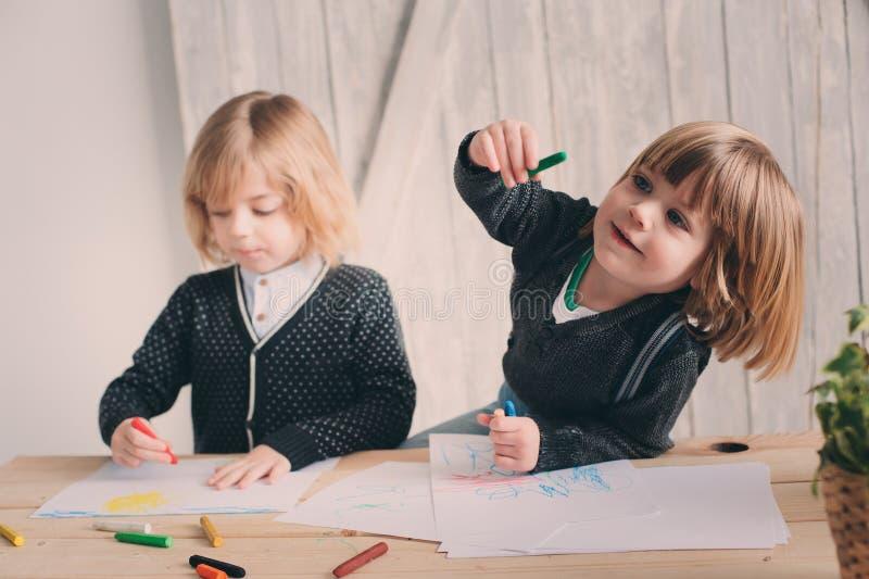 Zwei jüngere Brüder, die zusammen zu Hause zeichnen Glückliche Geschwister, die zusammen Zeit verbringen lizenzfreie stockfotos