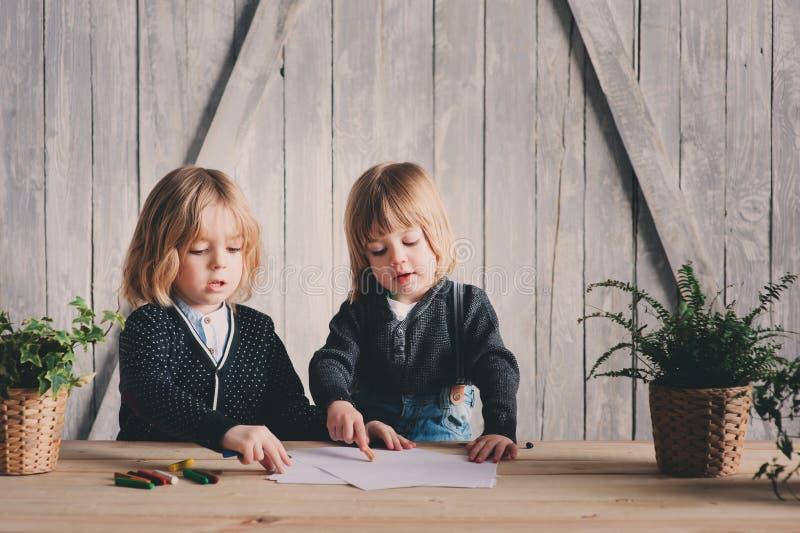 Zwei jüngere Brüder, die zusammen zu Hause zeichnen Glückliche Geschwister, die zusammen Zeit verbringen stockbilder