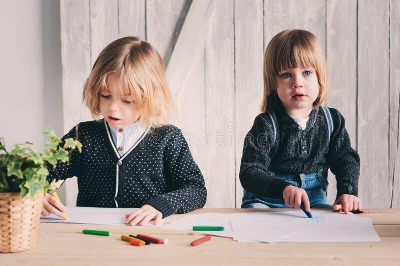 Zwei jüngere Brüder, die zusammen zu Hause zeichnen Glückliche Geschwister, die zusammen Zeit verbringen stockfotos