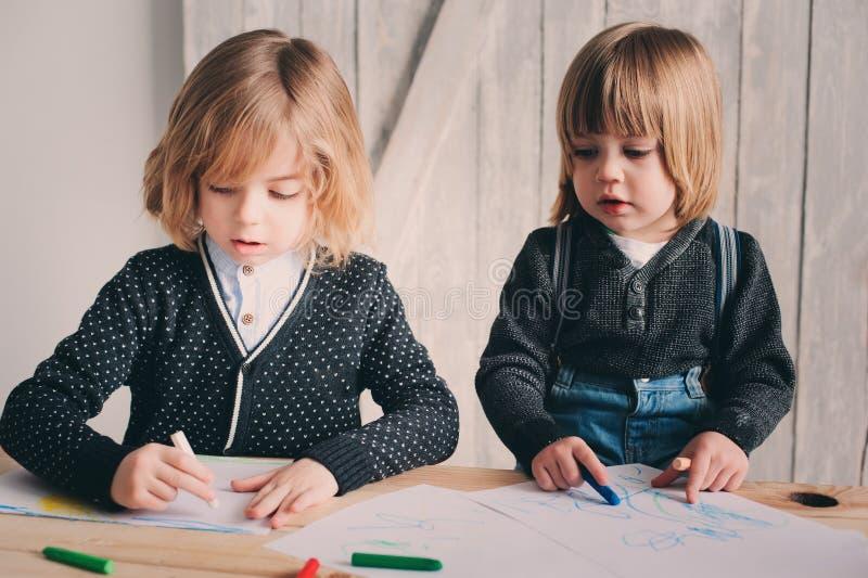 Zwei jüngere Brüder, die zusammen zu Hause zeichnen Glückliche Geschwister, die zusammen Zeit verbringen lizenzfreies stockbild