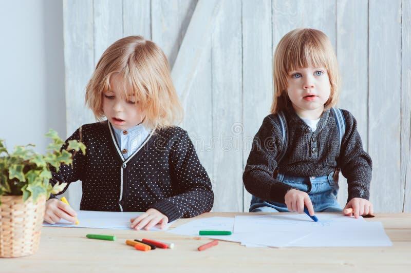Zwei jüngere Brüder, die zusammen zu Hause zeichnen Glückliche Geschwister, die zusammen Zeit verbringen lizenzfreie stockfotografie