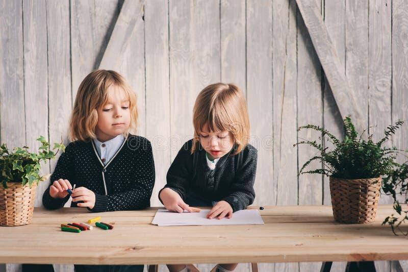 Zwei jüngere Brüder, die zusammen zu Hause zeichnen Glückliche Geschwister, die zusammen Zeit verbringen stockfotografie
