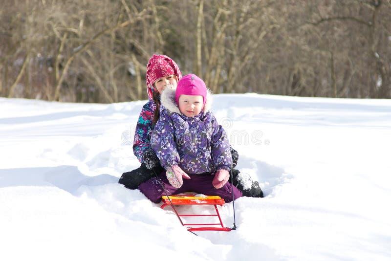Zwei jüngere Schwestern, die zusammen auf einem Schlitten in einer Schneewehe an einem klaren Wintertag sitzen stockbild