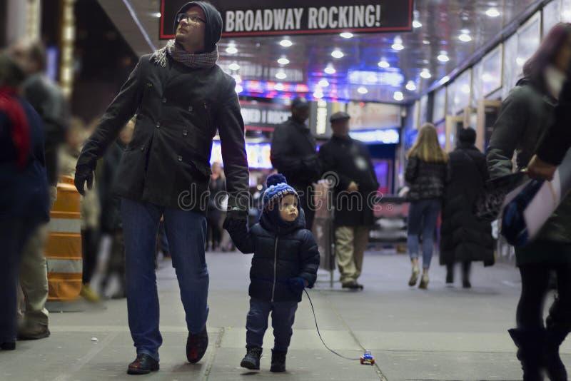 Zwei Jahre Kleinkind mit dem Vater, der auf Brodway in Manhattan am Abend geht stockfoto