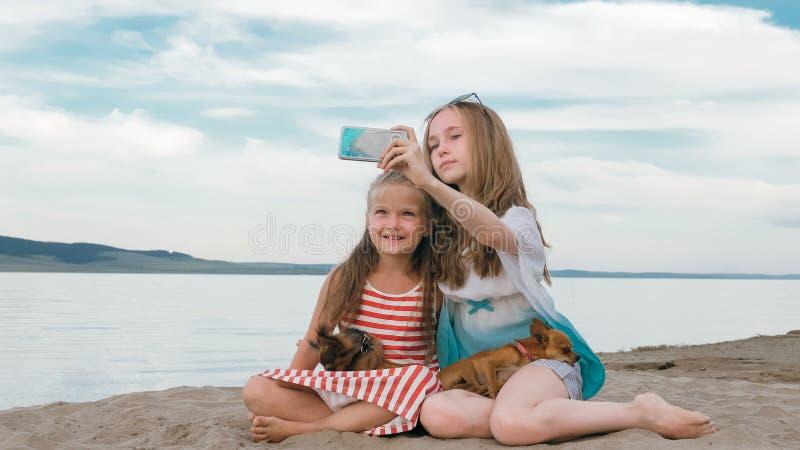 Zwei Jugend sitzen auf einem sandigen Strand, im Internet im Telefon lizenzfreie stockfotos