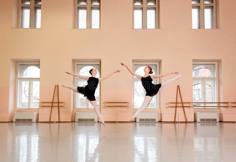 Zwei Jugendballerinen, die im großen Studio des klassischen Balletts üben lizenzfreies stockfoto