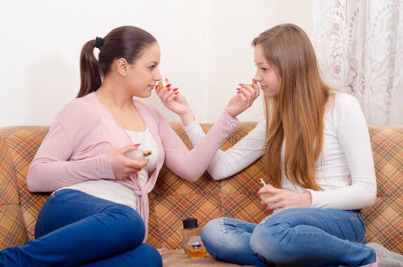 Schöne Jugendlichen, die Parfüme riechen lizenzfreie stockfotos