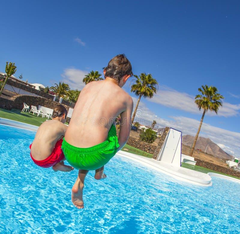 Zwei jugendlich Jungen, die in das blaue Pool springen stockfotos
