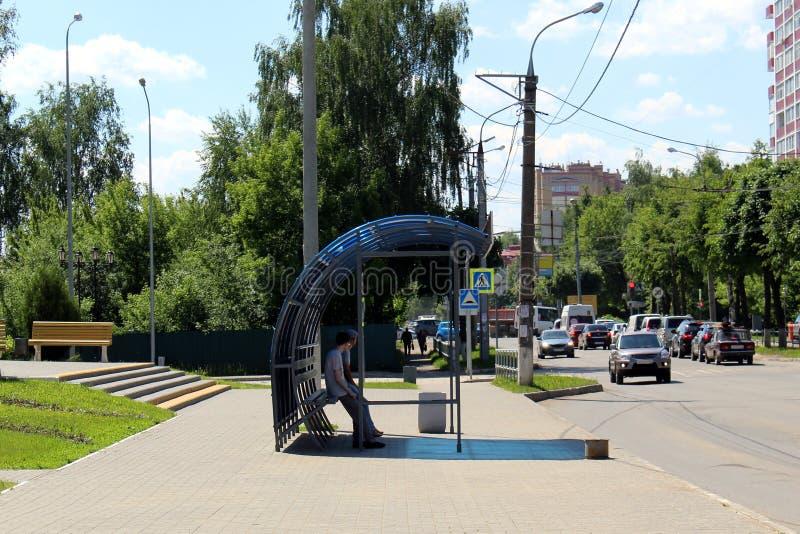 Zwei jugendlich Jungen sitzen an der Bushaltestelle und dem Wartung den Bus lizenzfreies stockbild