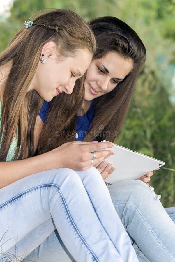 Zwei jugendlich Mädchen mit Ihrem Tablet-PC in der Natur lizenzfreie stockbilder
