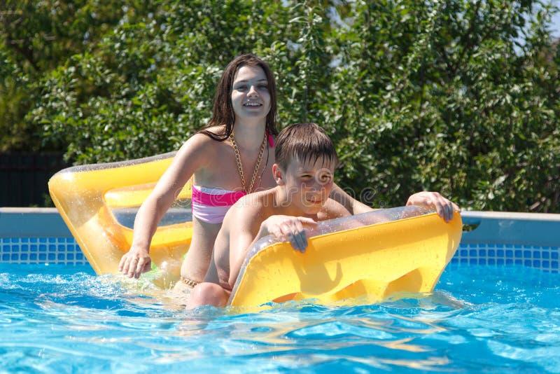 Zwei Jugendliche, die im Pool schwimmen stockfotografie
