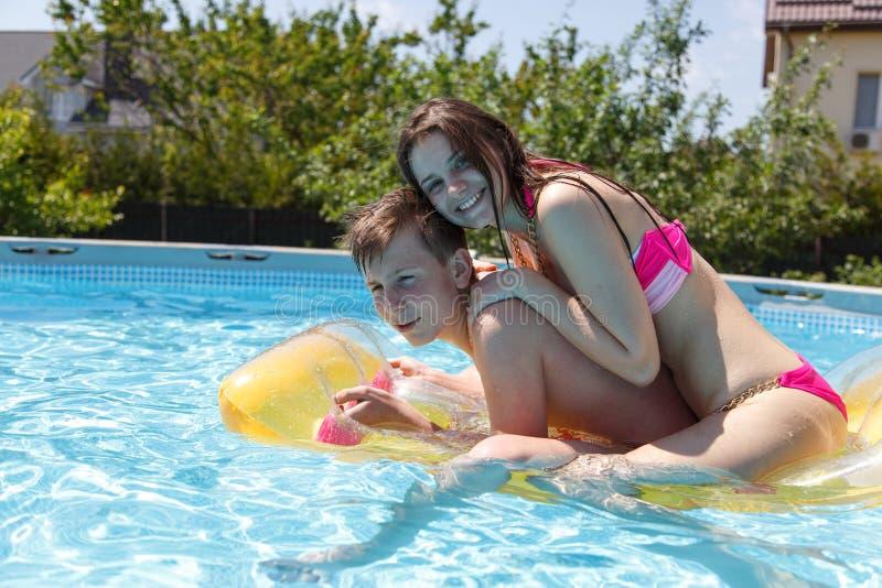 Zwei Jugendliche, die im Pool schwimmen lizenzfreies stockbild