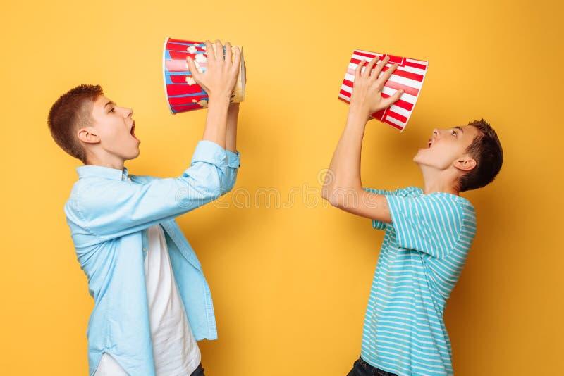 Zwei Jugendliche, die Popcorn essen und Spaß auf einem gelben Hintergrund haben stockfoto