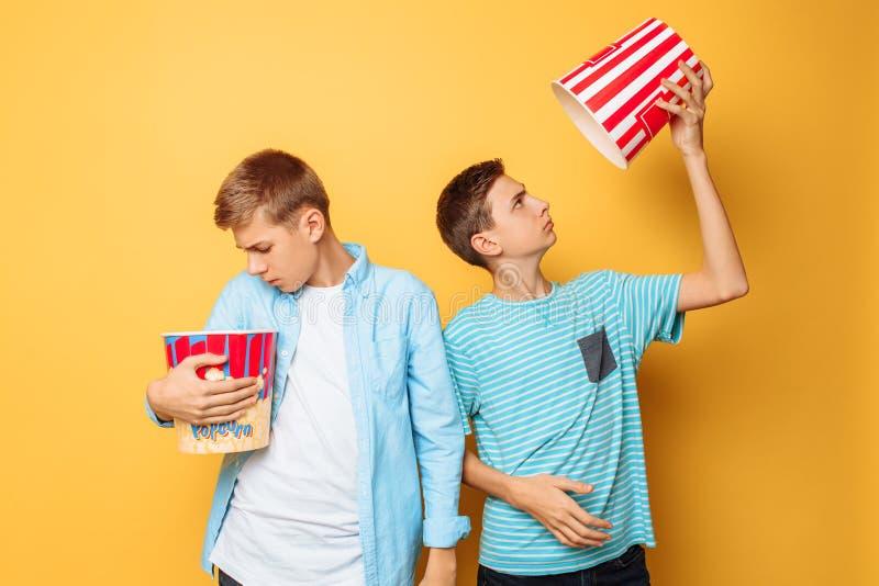 Zwei Jugendliche, die Popcorn essen und Spaß auf einem gelben Hintergrund haben stockfotografie