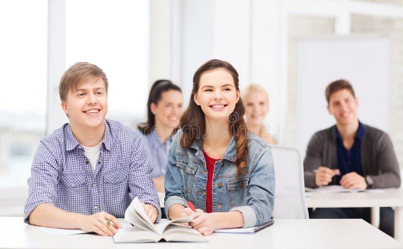 Zwei Jugendliche mit Notizbüchern und Buch in der Schule lizenzfreies stockfoto