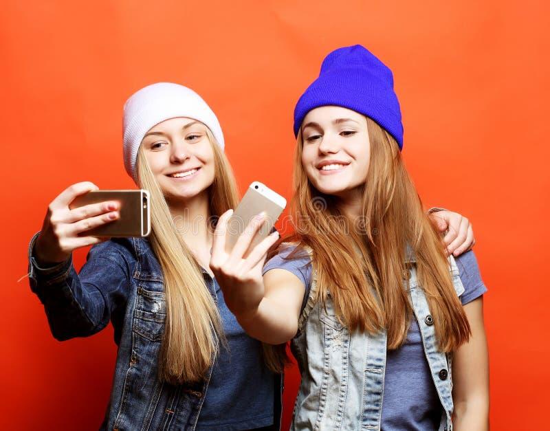 Zwei Jugendlichefreunde in der Hippie-Ausstattung machen selfie auf einem pho stockbild