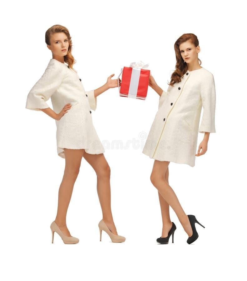 Zwei Jugendlichen in den weißen Mänteln mit Präsentkarton lizenzfreie stockbilder