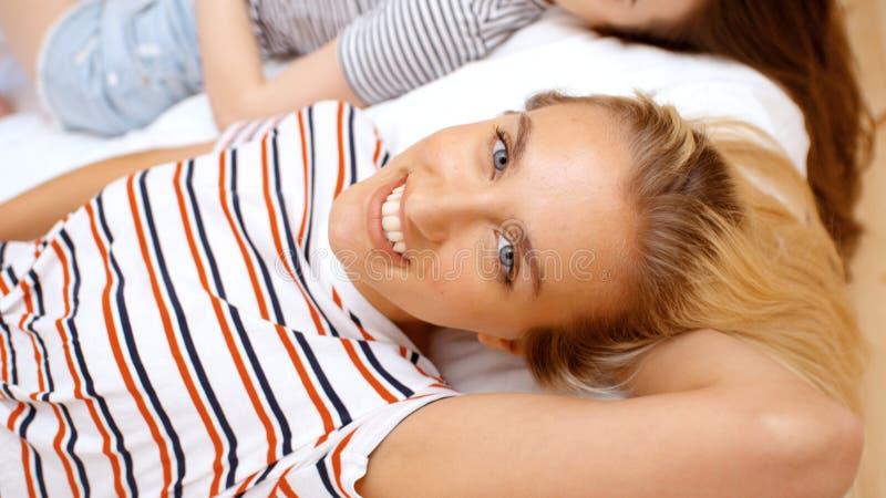 Zwei Jugendlichen, die auf Bett im gemütlichen Raum liegen und Spaß haben stockfotos