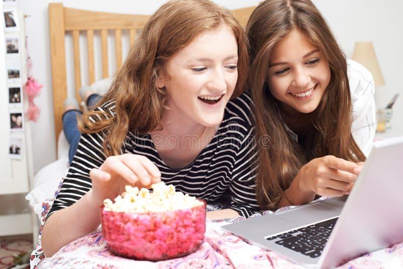 Zwei Jugendlichen, die Film auf Laptop im Schlafzimmer aufpassen stockbilder