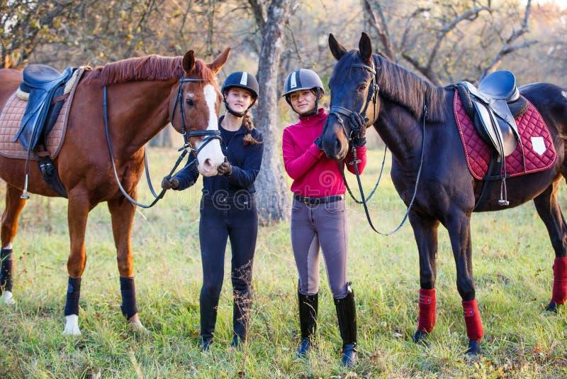 Zwei Jugendlichen mit ihrem Pferd im Park stockfotografie