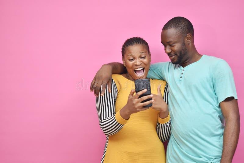 zwei junge afrikanische Freunde, Junge und Mädchen, die aufgeregt sind, wenn sie zusammen etwas auf ihrem Smartphone sehen lizenzfreies stockfoto