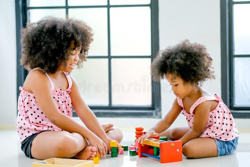 Zwei junge afrikanische Mädchen spielen Spielwaren zusammen mit Hauptfokus auf rechtem Seitenmädchen, die schauen, mit ihren Spie stockfoto