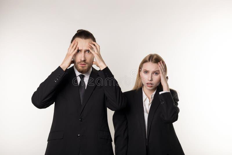 Zwei junge Angestellte in den schwarzen Anzügen, die mit den Händen auf Kopf, entlassene Arbeitskräfte nach Konkurs ihrer Firma s stockbild