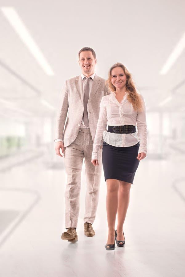 Zwei junge Angestellte oder ein Geschäftsmann, ein Mann und eine Frau, sicher gehen zweckmäßig entlang den Korridor im Büro stockfotos