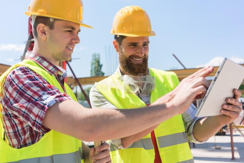 Zwei junge Arbeitnehmer, die ein Video aufpassen oder on-line--throu mitteilen stockbild