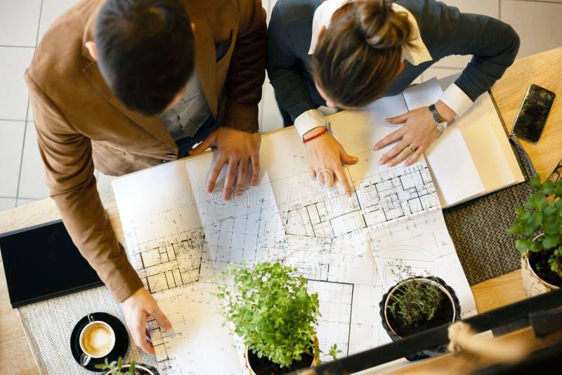 Zwei junge Architekten, die Baupläne während einer Sitzung in einem Büro besprechen stockbilder