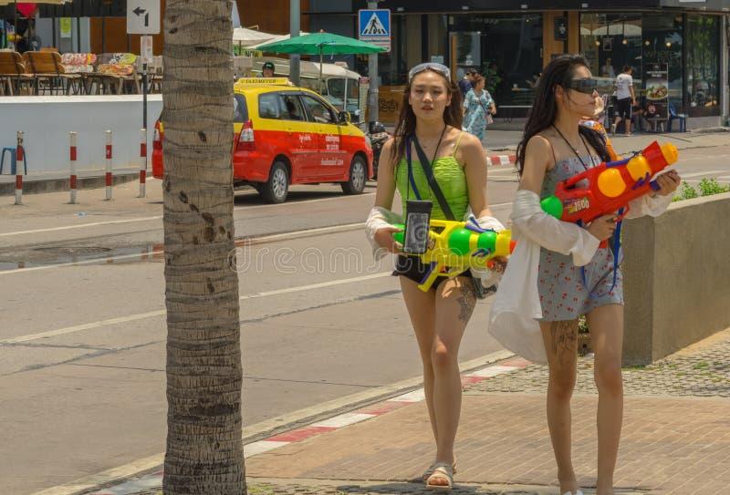 Zwei junge Asiatinnen waren armend mit den bunten Wasserpistolen zum Haben von Spaß in Songkran lizenzfreie stockfotos