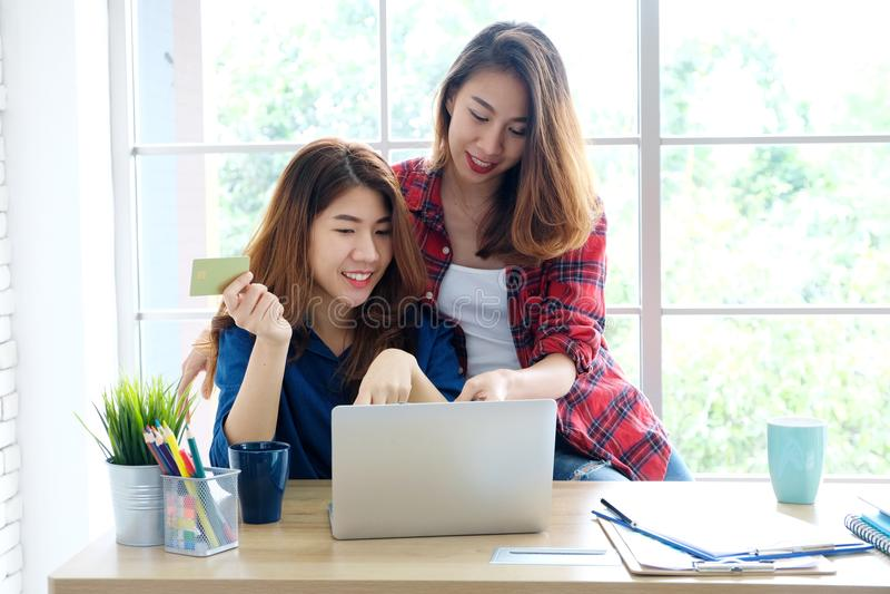 Zwei junge asiatische Frauen, die Kreditkarte halten und Laptop compu verwenden lizenzfreie stockfotografie