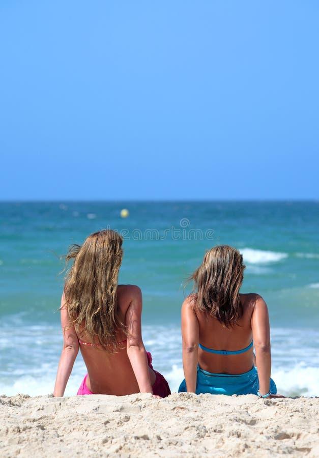 Zwei junge attraktive Frauen, die in der Sonne am Feiertag oder an VAC kühlen lizenzfreies stockfoto