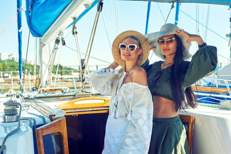 Zwei junge attraktive Frauen stehen auf einer Yacht an einem sonnigen Tag still stockfoto