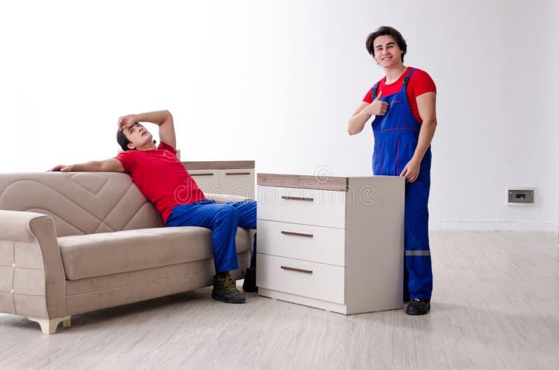 Zwei junge Auftragnehmerangestellte, die pers?nliches Eigentum bewegen stockfotos