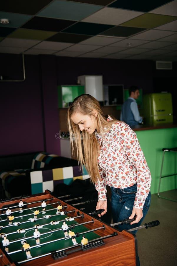 Zwei junge Büro-Leute, die Tabellen-Fußball-Spiel während ihrer Freizeit am Arbeitsplatz genießen lizenzfreies stockbild