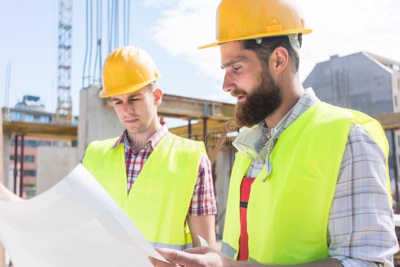 Zwei junge Bauarbeiter, die zusammen den Plan von a analysieren lizenzfreies stockbild