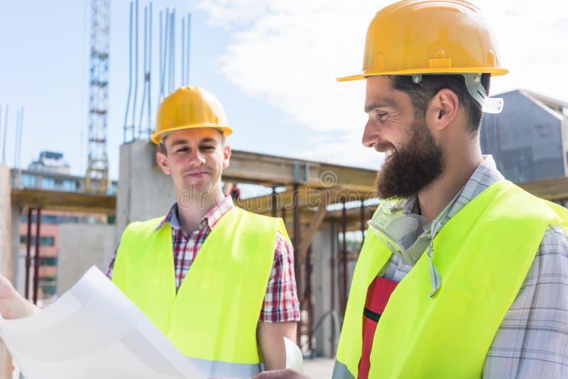 Zwei junge Bauarbeiter, die zusammen einen Plan analysieren lizenzfreie stockfotos