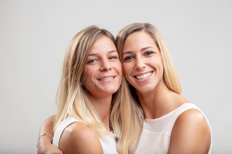 Zwei junge blonde Frauen in einer nahen Umarmung stockbilder