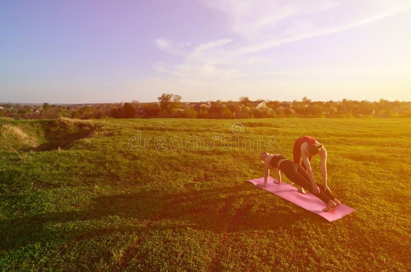 Zwei junge blonde Mädchen in den Sportklagen üben Yoga auf einem malerischen grünen Hügel lizenzfreie stockfotografie