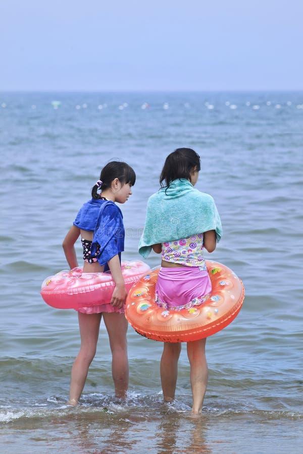 Zwei junge chinesische Mädchen mit einem Floss in einem blauen Meer Yantai, China lizenzfreie stockbilder