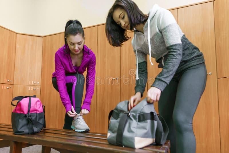 Zwei junge Eignungsfrauen in Umkleidekabine an der Turnhalle Eignung, Sport, Training, Leute, gesundes Lebensstilkonzept stockfoto